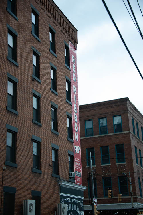 Brick building sign. Red Ribbon Pop. Strip District, Pittsburgh, Pennsylvania. April 28, 2018.